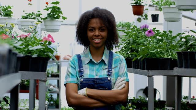 kadın bahçıvan kameraya gülümsüyor - orta plan plan türleri stok videoları ve detay görüntü çekimi