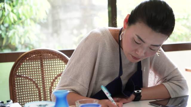 Documento de escritura de artista de cristal femenino - vídeo