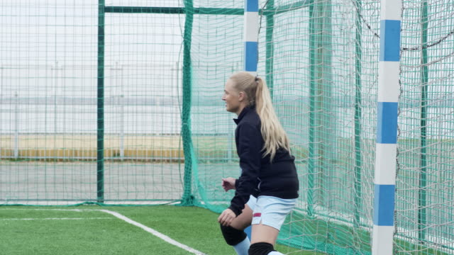 Female goalkeeper palming the ball away Young Caucasian sportswoman standing near soccer goalpost and waiting for attack, turning the ball away goal post stock videos & royalty-free footage