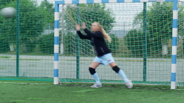 female goalkeeper saving her post Female goalkeeper standing on goal post, waiting for ball and palming it away goal post stock videos & royalty-free footage