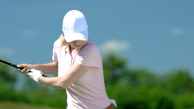 Female golf beginner player hitting shot and watching trajectory, slow-motion
