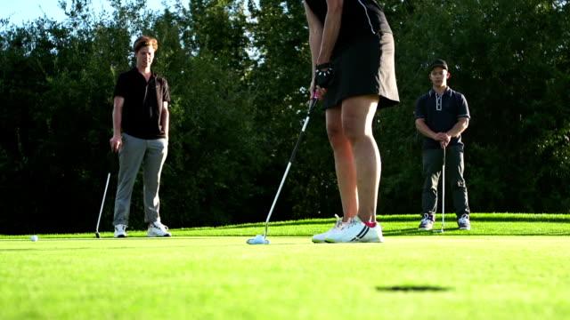 Female golfer makes a putt. video