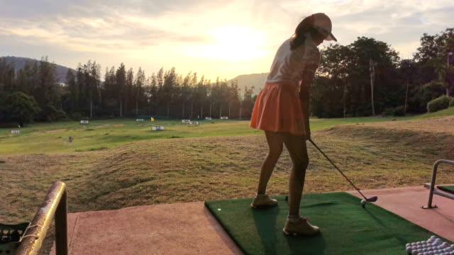 female golfer teeing off, time lapse - strzelać piłkę filmów i materiałów b-roll