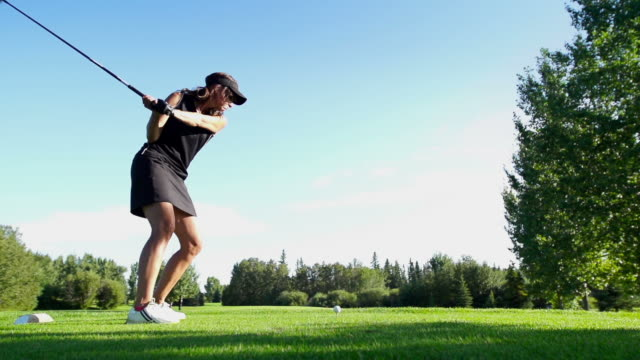 Female golfer tees off. video