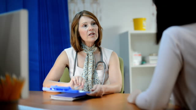 female gp chatting to female patient a mature female gp is sitting at her desk discussing what she sees on her computer screen with her female patient who is also sitting at the desk. nhs stock videos & royalty-free footage