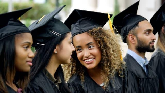Female graduates share a laugh during the keynote speech