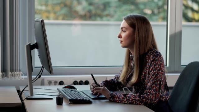 vídeos de stock e filmes b-roll de female graphic designer working in the office - contente