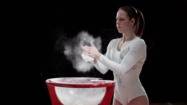 SLO MO Female gymnast clapping her chalky hands over the chalk bowl video