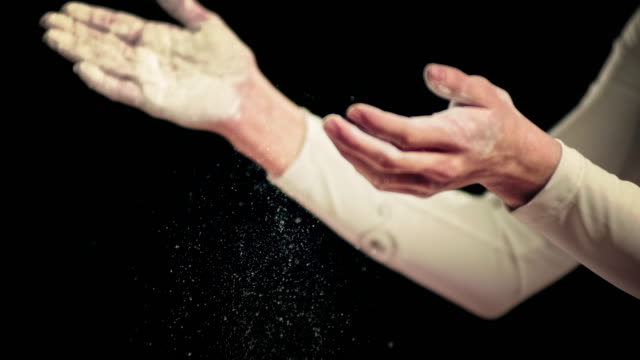 SLO MO Female gymnast clapping her hands to get the chalk off video