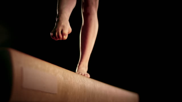 SLO MO Female gymnast doing a back walkover on the balance beam video