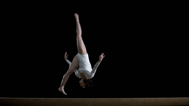 SLO MO Female gymnast doing a flip on balance beam