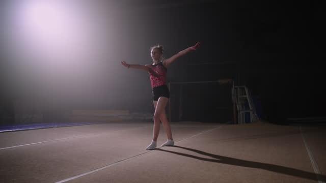 vídeos de stock, filmes e b-roll de ginasta feminina está realizando flips no chão da primavera, treinando em salão de ginástica sozinho, ginástica artística, competição júnior - ginástica