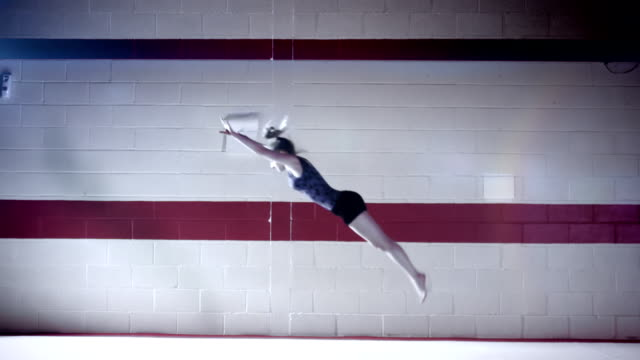 Female gymnast peforming floor exercise in slow motion video