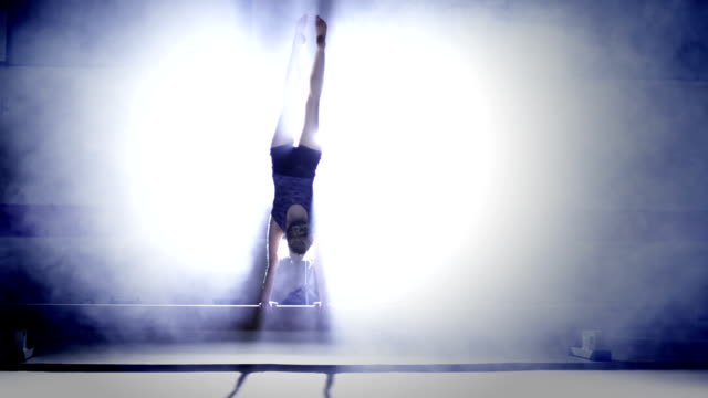 Female gymnast peforming on a balance beam in slow motion video