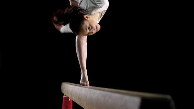SLO MO Female gymnast performing a flip on balance beam video