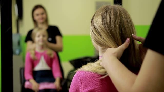 Female hairdresser arranging hairdo in barber shop video