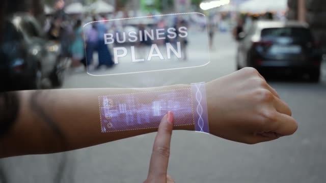 Female hand activates hologram Business plan