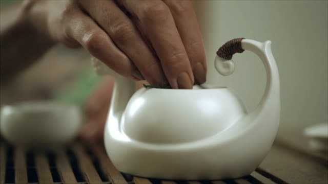 Female hand brew tea in teapot cup. Close up of brewing tea in teapot video