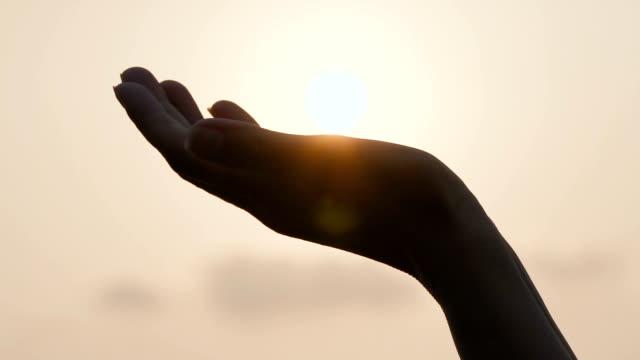 女性の手が太陽をキャッチ - 指点の映像素材/bロール