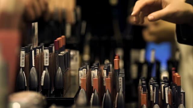kobieca ręka wybierająca kolor błyszczyka, przemysł kosmetyczny, najlepszy prezent, kobiecość - makeup filmów i materiałów b-roll