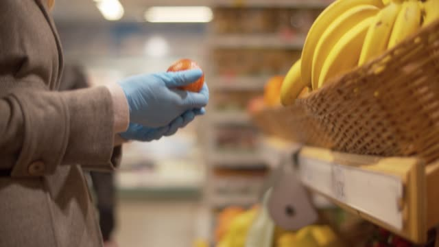 Female hand choosing oranges in the supermarket Close up hand of a woman in blue protective gloves choosing oranges in the supermarket. Coronavirus epidemic in the city. Covid-19 pandemic glove stock videos & royalty-free footage