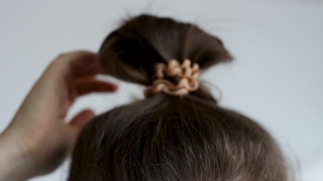 Female hand correct the bun on white background.