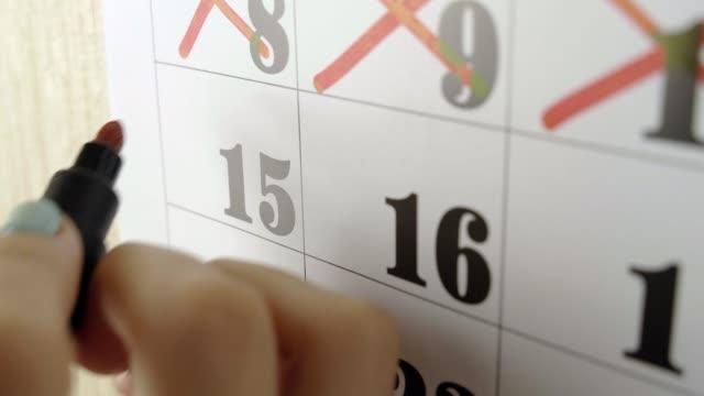 kvinnlig hand korsar med röd markör kalenderdagen 15. slow motion shot. närbild - korsform bildbanksvideor och videomaterial från bakom kulisserna
