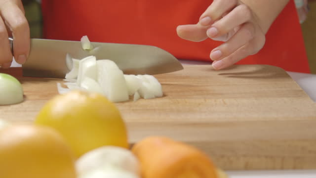 Female hand cuts onion carrot and orange on a wooden cutting board. video