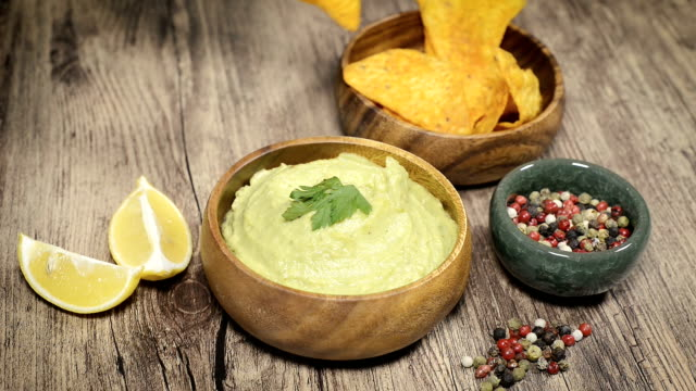 female hand dipping nacho into guacamole sauce - immergere video stock e b–roll