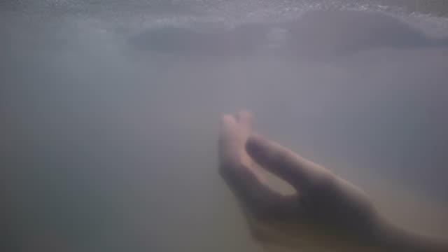 mano femminile annegata sott'acqua scura, vittima di omicidio, scena del crimine, primo - cadavere video stock e b–roll