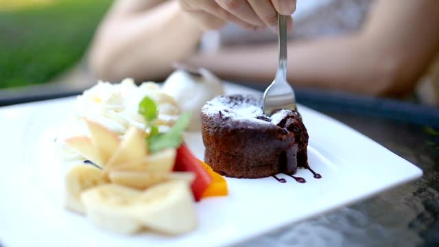 Mano de mujer comiendo pastel de chocolate lava en el parque exterior. - vídeo