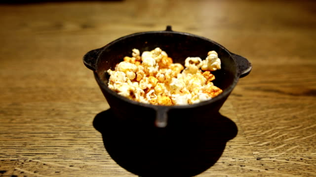 Female hand grabbing popcorn from metal bowl. Young girl tastes delicious spicy popcorn. video