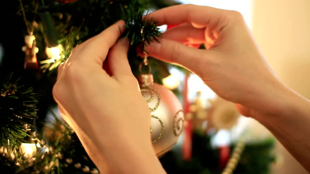 female hand hangs golden christmas ball on tree, close up - hänga bildbanksvideor och videomaterial från bakom kulisserna