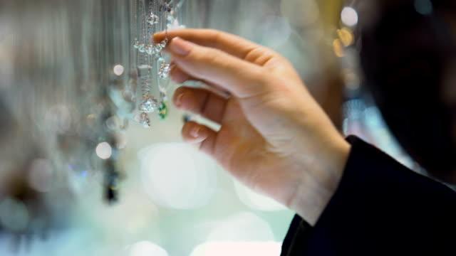 ダイヤモンド ペンダント、高級ショッピング モールでジュエリーの品揃えを持っている女性の手 ビデオ