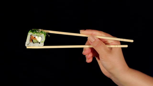 Female hand holding sushi with chopsticks in dark. video