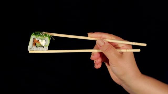 Mujer mano sushi con los palillos en oscuridad. - vídeo