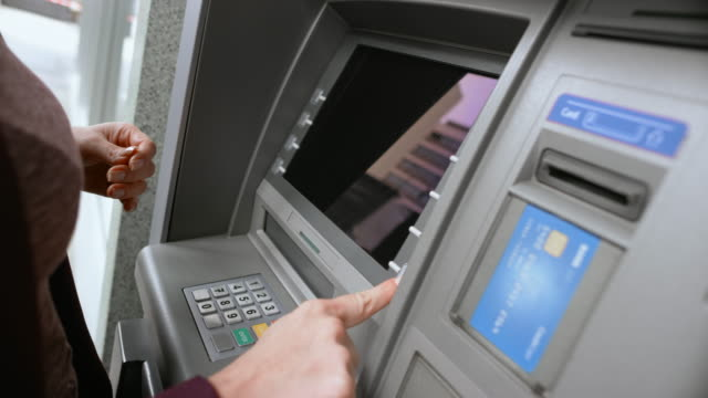 ld female hand inserting a bank card into the atm slot, entering pin number and choosing from the display menu - banks and atms stock videos & royalty-free footage