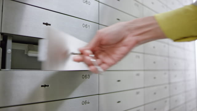 ds female hand inserting a box into the safe deposit box at the bank and locking it - safes and vaults stock videos & royalty-free footage