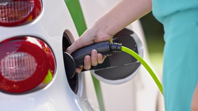 SLO MO DS Female hand inserting plug into electric car Slow motion close up shot of a female hand inserting a plug into an electric car. alternative fuel vehicle videos stock videos & royalty-free footage