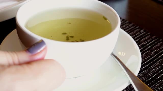女性の手はカップを持ち上げる - ソーサー点の映像素材/bロール