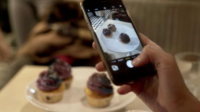 vídeos y material grabado en eventos de stock de mujer mano haciendo foto de postre dulce en el teléfono móvil en la cafetería - gastronomía fina