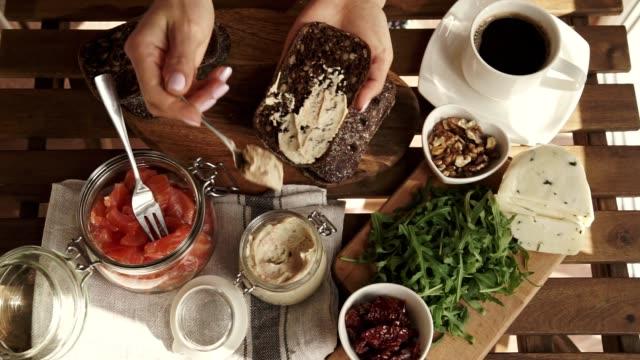 kvinnlig hand att göra smörgås med hummus och lax för frukost. ovanifrån. solig dag - cheese sandwich bildbanksvideor och videomaterial från bakom kulisserna