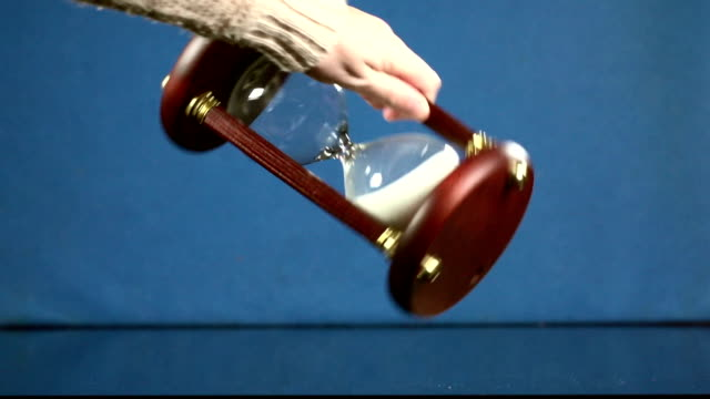 Female hand moves into frame from the left and turns over an old-fashioned hour glass, in which the sand then starts running again. video