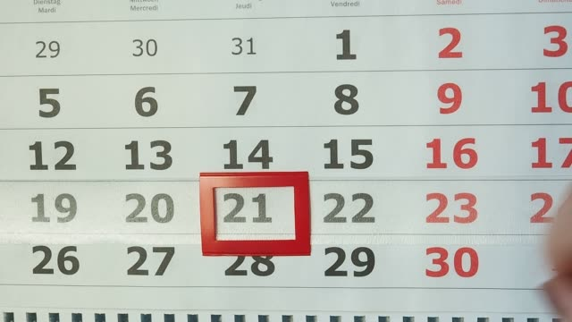 Female hand moves the number on the calendar selector. New date day.