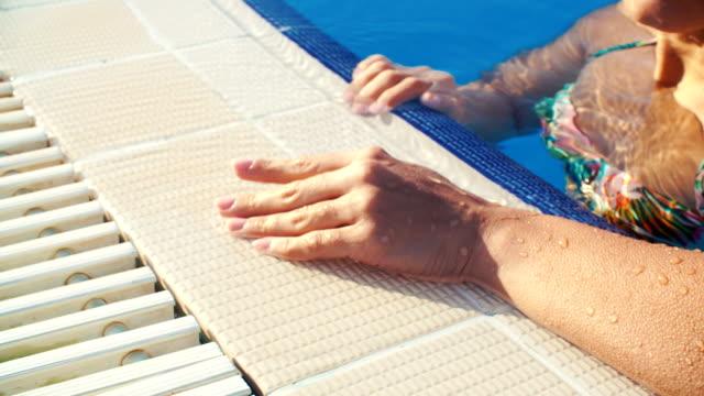 vídeos de stock e filmes b-roll de female hand on edge of pool on sunny summer day closeup - liga desportiva