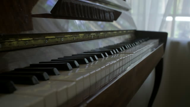 Female hand opening wooden piano cover. Old-fashioned piano indoors.