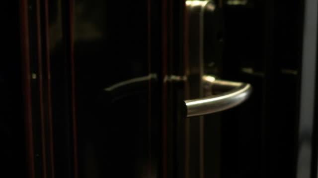 vídeos y material grabado en eventos de stock de mano femenina se abre la puerta al apartamento de lujo o a la habitación del hotel. - manija
