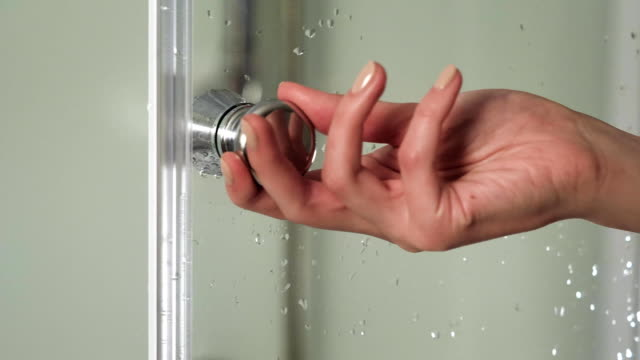 Female hand opens the door in the shower cabin. Woman hold handle bathroom cabin with right hand. Detail of a modern glass shower cabin. Shower video