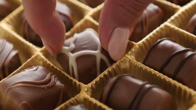 多くの異なるお菓子 4 k 2160 p 30 fps ultrahd 映像 - アソート チョコレート ボックス 3840 x 2160 uhd 映像からワンピースを選ぶ女性の豪華なセットを女性の手 - バレンタイン チョコ点の映像素材/bロール