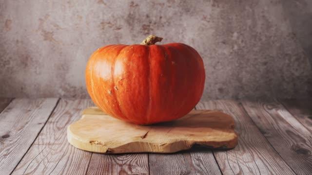 female hand placing a big orange pumpkin on wooden board - pumpkin pie стоковые видео и кадры b-roll